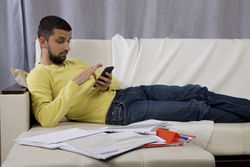 stock-photo-procrastination-a-man-lying-on-the-couch-and-looking-at-the-phone-he-does-not-want-to-work-471015626